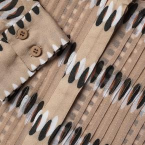 Lækker skjorte,  i sandfarvet,  aldrig brugt.  Modellen hedder Erick  Den er af 100 % viscose   Længde 90 cm Brystmål 2x53-54 cm  BYTTER IKKE  !!!  Prisen er 475 kr Handler mobil pay