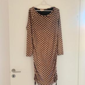 Blødt velour med snøre i begge sider, så kan justere kjolens længde og fit. Min mening ville være at en str. 38/M også kan passe den.