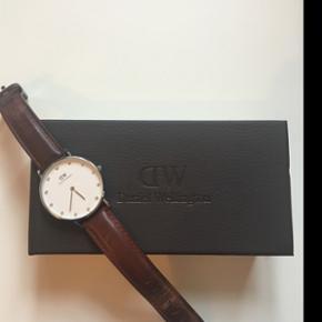 Sælger mit Daniel Wellington ur, da jeg ikke bruger det nok.Det er 1,5 år gammelt, men fejler intet. Urskiven er med sten, og er udgået, og remmen er brun.  Np: Ca 1200-, BYD! (Sender og mødes)