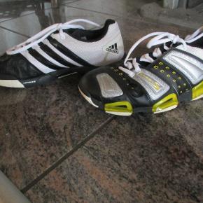 Flotte Adidas sportssko i sort hvide, med seje gule effekt hen ad siden,De er brugt til indendørs idræt, derfor fremstår de i en rigtig flot stand på trods af at de er brugte, som billederne forhåbentlig viser.