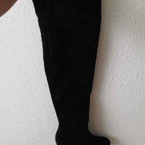Hælen måler 7 cm, bredte øverst er 22,5 cm, og længden på hele skoen er 64 cm. De er gået med en enkelt gang.