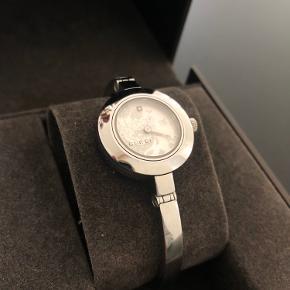 """Gucci """"Flora"""" 105 i rustfrit stål (sølv). Uret har en blomst i selve urskiven, der changerer. Der er brugsspor, dog ingen ridser på selve urskiven. Sender gerne flere billeder ved interesse😊"""