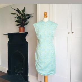 Flot vintage kjole med kinakrave fra 60'erne . Den er i virkelig god, vintage stand. Den er i flot brokade stof. Der er et lille hul i foret indeni, men som sagt ikke noget man kan se når den er på.