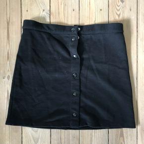 Fin, sort nederdel med knapper.  Nederdelen knappes foran og har en lomme på bagsiden.  Størrelsen svarer til s/ 14 år.  Mål.  Længde: ca. 41 cm. fra talje til kant  Bredde: ca. 38 cm.  Nederdelen er lavet af 100% bomuld.