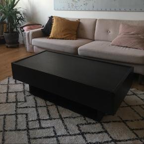 """Sort træ-sofabord fra IKEA. Originalt var der en glasplade på toppen, men den er blevet smidt ud. Vi har dog været glade for bordet uden glasplade.Der er to store skuffer i hver sin side med massere af plads. Der er en """"hylde"""" under bordet, fx til bøger. Grundet manglende glasplade kan man evt smide nogle kakler/fliser på (3.billede), hvis man ønsker at gøre det unikt. BYD!"""