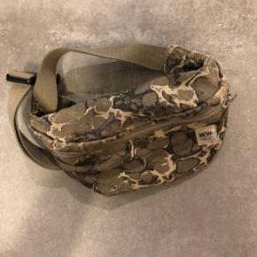 Rigtigt fed crossbody-taske fra Wood Wood i millitærfarver. Den er god, men brugt og i grønne farver. Den ser meget gul ud på billedet, men er mere en knækket hvid rigtigt.