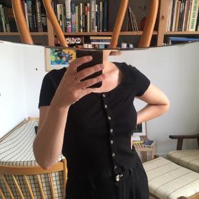 Fin t-shirt i bomuld med knapper foran. Kort model.  Kan afhentes på Amager (ved Christmas Møllers Plads) eller sendes på købers regning.
