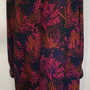 Super flot kjole i sort med smukt farverigt print, der passer fint til efteråret. Kjolen har læg ved halsudskæringen, lille åbning i ryggen med knaplukning, slids foran i højre side og ribærmer med en glimmer stribe. Kjolen er kun brugt ganske lidt og fremstår derfor næsten som ny 🌸