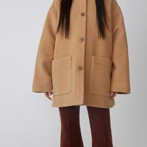 short cocoon coat Stockholm's Acne Studios create outerwear prepared for the coldest days, with traditional silhouettes re-imaged as sleek, modern pieces. Crafted from a warming camel brown wool blend, this short cocoon coat features an oversized fit, a classic collar, dropped shoulders and two front pockets. Sammensætning For: Viskose 100% Ydre: Uld 70%, Nylon 26%, Andre Fibre 4%