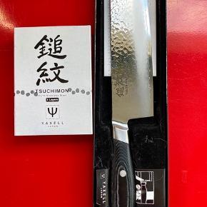 """Yaxell Tsuchimon Nakiri grøntsagshakker. Model no. 36704. Længde 180mm/7 tommer. Ryggen 2mm. 230 g. 12° graders vinkel. Butikspris 1.099 kr. Sælges 899 kr.  Ubrugt gaver. Fik knive i indflyttergave, men har allerede de knive jeg skal bruge, som også er fantastiske Yaxell.  Håndlavet i Japan af 3 lag højkvalitets VG-10 hammerslået rustfri carbonstål. Tsuchimon navnet hentyder til """"hammerslået overflade af bladet"""". Det kan hjælpe med at de madvarer du skærer, lettere slipper bladet. Katana sværd bølgeline ved ægget giver imponerende udseende.   Skæft/håndtag i hårdfør & vandafvisende Micarta (blanding af harpiks & hør). Micarta ligner & føles som træ, men er ligeså hygiejnisk & holdbar som plast. Monteret med rustfrie nitter som giver optimale holdbarhed.   Hardness Rockwell HRC 61. Vestlige/tyske/franske knive har typisk HRC 55-58.  Høj HRC gør at ægget er hårdere, slidstærkt, skarpere & holder skarpheden længere. Hvorfor kniven ikke skal slibes så ofte.  Yaxell har vundet utallige tests/priser.  https://www.jpknive.dk/serier/yaxell-tsuchimon/ https://madetmere.dk/yaxell-den-skarpeste-kniv-i-skuffen/ https://jv.dk/artikel/styrke-og-skarphed-kokken-og-sliberen-tester-knive  Jeg har Facebook siden 2007 & Nem-ID valideret på DBA, så du kan trygt handle med mig. Foretrækker fysisk møde i Aarhus/Århus men kan sende. Kun MobilePay & kontanter.  Vh Tim mobil 31126647"""