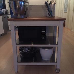 Praktisk rullebord  Bordpladen er massiv eg. Benene er hvidmalet træ. Hylderne er rustfri stål. Rullebordet har to hjul i den ene side og to ben i den anden og kan derfor nemt flyttes.   Rullebordet kan bruges i forlængelse af køkkenbord eller som afsætnings- og opbevaringsplads andre steder.   Bredde: 79 cm Dybde: 51 cm Højde: 90 cm  Rullebordet sælges for mine forældre. Det er placeret i Ebeltoft.