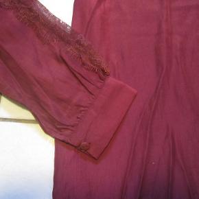 Smuk meget let tunika i satinkvalitet fra Nü Staff med den flotteste blondedetalje ned langs begge ærmer.