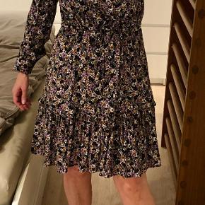 Der er et bindebånd syet fast i kjolen, så den kan strammes ind i taljen.
