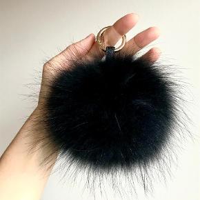 Varetype: Stor ægte Pelskvast nøglering, vedhæng Størrelse: Stor Farve: Sort  Stor lækker fyldig ægte pelskvast til at hænge på tasken.  Måler ca 18cm