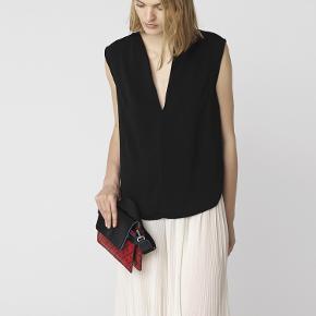 Style Louppa Top er fremstillet i et let gennemsigtigt stof med en almindelig pasform. Den har en grafisk halsudskæring foran med slids, som understreges af sømmen foran.   Kvaliteten er 100 polyester Vaskeanvisning: håndvask maskine  550pp Bytter ikke
