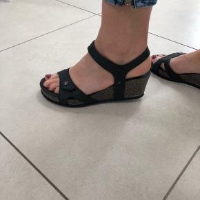 Blød og let sandal i sort læder og korkhæl. Højde ca. 5,5 cm. Ergonomisk og blød. Velcrolukning to steder. Helt nye, sælges stadig i butikkerne, 899 kr.
