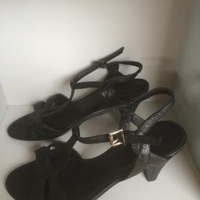 Mærke: Billi Bi Størrelse: 38.5 Farve: sort Materiale: læder Sandalen. Har remme og mellem høj hæl Stand: Brugt få gange og fremstår derfor som næsten nye.   Sælges 200;kr.