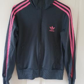 Fed mørkegrå cardigan med pink striber og mørkt Adidas-logo på ryggen. Brugt en del for nogle år siden. I fin stand, lidt slid på lynlåsen (se billede) Tager ikke billede af tøjet på. 🌺