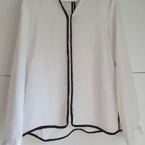 Hvid skjorte med sorte striber. Har kun været brugt få gange.