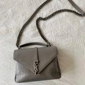 """Saint Laurent Medium College taske i """"Grey Crocodile embossed leather"""". Tasken er købt secondhand, kvittering haves desværre ikke længere, men alt andet medfølger inkl. autenticitetskort.  Jeg får desværre ikke brugt den nok, og derfor sælges den. Det eneste slid er lidt på nogle af hjørnerne og kæden, som er uundgåeligt. Mp: 7600kr :-)"""