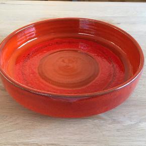 Flot Klavs Encke keramikfad med orange changerende glasur. Diameter 27 cm, højde 6,5 cm. Fin stand. Ingen skår, revner eller afslag. Et par små aldersrelaterede/brugsrelaterede overfladeskrammer inden i fadet.  Vintage, 70'erne, fad, stentøj   Jeg sælger også bl.a. vintagetøj + unikke ting til hjemmet, og jeg giver mængderabat.
