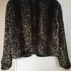"""Super fin kort jakke i leopardprintet faux fur / leopard pels. Den har et enkelt snit med kantet i sort """"læder"""". Den har et super klædeligt snit og er ideel som overgangsjakke eller til festlige lejligheder. Str 38 men passes af flere pga snittet. Kom med et bud. NP: 1200kr.  Varen befinder sig i 9520 Skørping. Sender med DAO.  Se også min øvrige annoncer. Jeg sælger tøj, sko og accessories. Pt er min shop fuld af vintagekup, high street fund og mærkevarer i mange forskellige str. Kig forbi og spøg endelig!"""