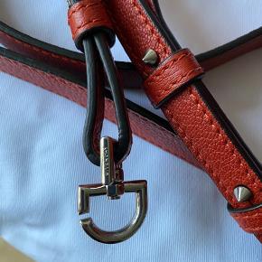 Givenchy mini antigona håndtaske/skuldertaske/crossbody taske med aftagelig strop. Tasken har været i brug max 5 timer og derfor er standen sat som aldrig brugt. Kommer fra et ikke ryger hjem og ikke dyre hjem. Æske, dustbag, certifikat, strop medfølger.  Str : 28 x 13 x 19 cm Composition: 100% Calfskin leather Lining : 100% Cotton. Farve: burnr orange   NP: 9675  By Givenchy: Mini Antigona bag in satchel leather. Trapezoid shape with triangular GIVENCHY patch, oversized zip and metal details. Adjustable and removable shoulder strap. Two flat pockets and one zippered pocket inside. made in Italy.  Respekter venligst at jeg ikke bytter og køber betaler porto samt gebyr ved tspay.