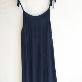 Mørkeblå Monki kjole med tynde stropper, der kan justeres. Går til lige over knæet.