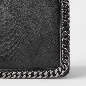 Fin sort taske med imiteret pels og sølvkæde fra zara. Tasken måler 17 x 28 x 9.