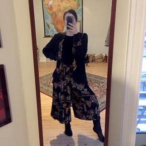 Vintage buksesæt med let jakke i sort flagrende materiale med funky mønsterdetaljer. Højtaljede culottes 3/4 længde bukser i mønstret materiale, elastik i taljen. Mærke: Tove Bonde. Passer str. S.