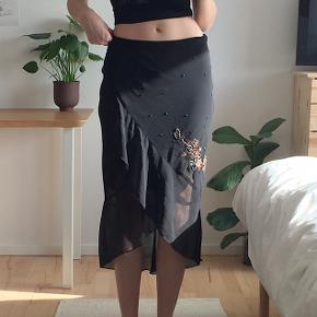 Vintage sort 00'er nederdel med perlebroderi og flæser. God stand. Nederdelen er str. 38, men jeg er en 36 til reference.  Tager kun imod bud i privatbesked.