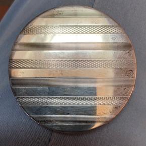 Tretårnet sølv pudderdåse - måske nok 50 år.  Rund lille fin pudderdåse med to forskellige striber på front - glat sølv på bagsiden. Fremstår tydeligt med tre tårne og stempel .  Diameter 6 cm.   Portobetales af køber med 45 kr.