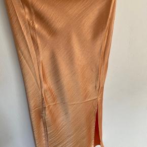 Super flot orange satin nederdel. Den har en kobber skær i sig da det er satin. Den har to slids i nederst og i hver side. Det er to lowkey slids og rigtig flot🧡