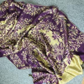 Smukt tørklæde i lilla/guld/glimmer  Har aldrig været brugt   Mål: L: 178 cm B: 69 cm  Sælges for 110kr