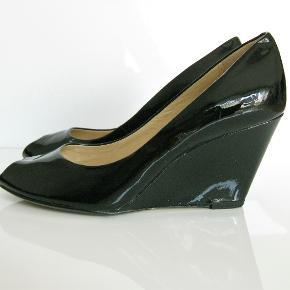 Elegante sorte laksko fra Clarks i str. 37 med 8 cm høj hæl. Brugt én gang. Fejler intet, har ingen ridser i lakken og er så gode som ny.  Oprindelig købspris: 1.199 kr.  Kan afhentes på Amager nær Amagerbro metro eller sendes med DAO (45 kr).