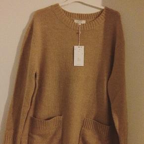 Lang strik bluse/kjole med store lommer foran. Ny med mærke. Størrelsen er one size. Farven er mørk beige. Jeg er small og synes den er for stor. Derfor er den kun prøvet på. Porto oven i prisen. :-)