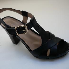 Smukke sandaler fra franske Minelli (IKKE Billi Bi, men de minder meget om Billi Bi i kvalitet og pasform) Hælhøjde 9,5 cm, men med 1,5 cm plateau i forfoden føles de ikke så høje og sidder fantastisk på foden. Lidt store i størrelsen, som en 38,5. Zoom ind på sidste billede og se at hælen er i mørkt træ (ikke helt sort).