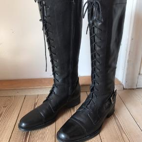 Flotte lange støvler med snøre foran. Kan reguleres med denne men lukkes med lynlås. Skind.