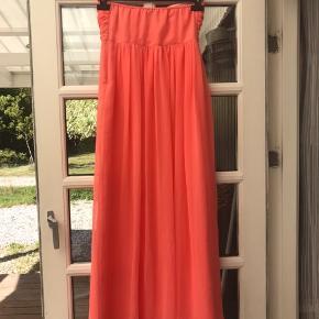 Super flot kjole i coral farve. Vatteret bryststykke med gummikant så den ikke glider ned. Brugt og vasket en enkelt gang.