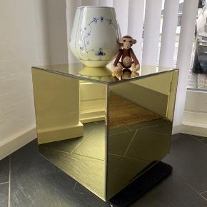 AYTM Speculum Mirror bord, lille Super smukt spejlbord fra det danske AYTM. Det flotte spejlbord i kubeform, der kan pynte ethvert rum. Dette Speculum bord er den lille model i farven guld. Virkeligt smukt som sidebord eller i et lidt mørkere hjørne.  NB!! Der er lidt skjolder rundt i kanterne på nogle af siderne pga lim (forsøgt vist på billederne) deraf den lave pris!! Men bordet er stadig mega smukt!! Og alt efter placering, så ses skjolderne altså ikke.   Bordet er ubrugt, kun pakket ud for at tage billeder (men sælges da vi ikke kan få det passet ind) skal lige pudses op efter fingeraftryk.   Materialer Kantlimet hærdet spejlglas Størrelse H40 x L38 x B38 cm  Slået op på andre sider. Afhentes i Skanderborg.