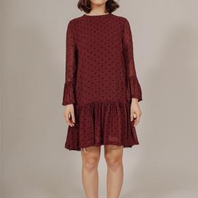 Smuk kjole fra Ganni i vinrød med prikker. Materiale: Viskose Med flæsedetaljer og trekvartærmer Brugt få gange, fremstår som ny Passes af str. M-L