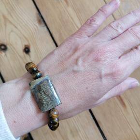 Armbånd med natursten. Tigerøje.  Diameter: 7mm  Firkantet sten: 2,5 x 2 cm Smykke elastik, hvorved armbåndet passer til alle str. håndled. Aldrig brugt.  Kan afhentes i Esbjerg eller sendes på købers regning og ansvar.