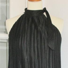 Sød plisséret sort kjole, som er plisséret i hele kjolens længde. Fast halskant med sløjfe. Kjolen har en 20 cm bred flæse forneden. Materialet er polyester  Brystvidde: Flexibel Længde: 95 cm  Ingen byt, og prisen er fast