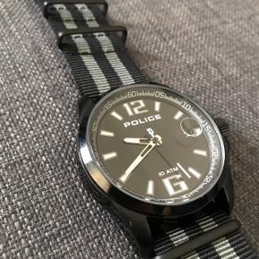 Sælger mit Police ur da jeg ikke længere får det brugt.  Monteret ny sort/grå NATO rem samt nyt batteri. Bemærk få brugsspor (bla nederste venstre hjørne på billede 2) Mere info på sidste billede.  Pris : 500 kr Befinder sig på Amagerbro eller 6800 Varde