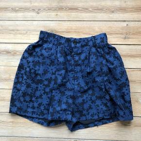 Smukke ballon-shorts fra Julien David. .    Shortsene er højtaljet og lukkes med lynlås og knap. De har fire lommer. To foran og to bagi der lukkes med to kapper.    Kun brugt én gang.   Mål Længde: ca. 41 cm Bredde (taljen): ca. 35 cm.