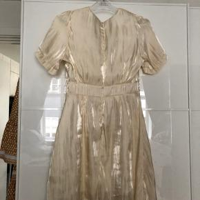 Flot lyst guld/beige kjole i et skinnede stof med knapper foran og lukkes bagpå med lynlås.   Jeg synes den klør lidt pga syningerne, så har kun brugt den én gang derfor er prisen også sat derefter   Fast pris 150kr ekskl porto
