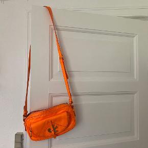 Flot neon orange Marc by Marc Jacobs taske med lang justerbar rem og mange små rum. Er brugt men fin. Se flere billeder i kommentarsporet 🧡