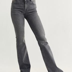 Flare jeans fra Mango i str 38. Bukserne er lavtaljet og har lange bukseben og er i en jeans-grå farve.