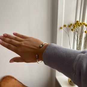 Et fint sølv armbånd med gulddetaljer 🌸 Materialet er nok jern 🤷🏼♀️ Størrelsen passer alle, da materialet kan bøjes og justeres