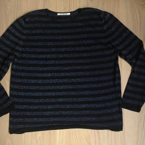 Fin bluse i sort med mørkeblå striber. Blusen har sølvtråde over det hele. Blusen er i 70% viscose, 16 % polyamid og 14 % metallic yarn.